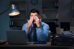Anställd som sent arbetar på natten på den viktiga rapporten Arkivfoto