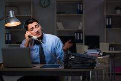 Anställd som sent arbetar på natten på den viktiga rapporten Fotografering för Bildbyråer