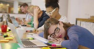 Anställd som sover på tabellen med coworkers lager videofilmer