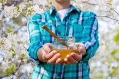 Anställd som visar honungen i den glass krukan royaltyfri foto