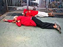 Anställda av stationen som sover rätt på trottoaren av järnvägsstationen royaltyfri foto