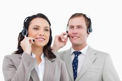 Anställda för telefonhjälpskrivbord med hörlurar med mikrofon Arkivbild
