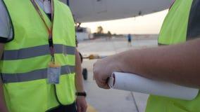 Anställda i gul löst skjortbröst skakar händer Flygplatsarbetare skakar händer Teknikerer skakar händer, når de har kontrollerat  Fotografering för Bildbyråer