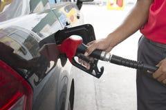 Anställda kontrollerade bränslepumpen på bensinstationen Royaltyfria Bilder