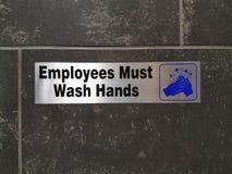 Anställda måste tvätta händer undertecknar på badrumväggen arkivfoto