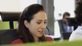 Anställda som arbetar i call centerkontor med hörlurar med mikrofon lager videofilmer
