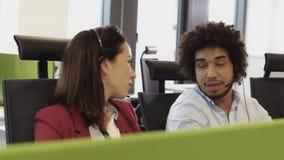 Anställda som arbetar i call centerkontor med hörlurar med mikrofon arkivfilmer
