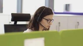 Anställda som arbetar i call centerkontor med hörlurar med mikrofon stock video