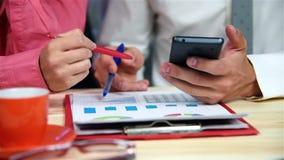 Anställda som bläddrar rapporten på mobiltelefonen stock video