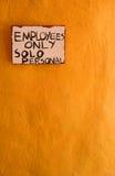 Anställda undertecknar endast på den gula/orange väggen Royaltyfri Fotografi
