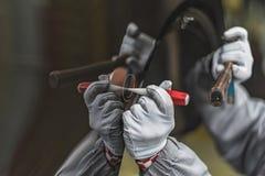 Anställdbilkroppen som målning shoppar, avlägsnar en liten metalldefekt royaltyfri foto