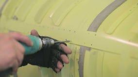 Anställdflygplanproduktionsanläggningen borrar hål i flygkropp av flygplan lager videofilmer