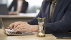 Anställdmaskinskrivning på bärbara datorn på skrivbordet, timglas som sipprar, att närma sig för stopptid lager videofilmer