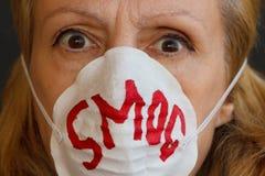 Anstarrende Augen einer Frau aus Angst vor Smog Lizenzfreie Stockfotografie