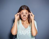 Anstarrende junge Frau, die über Gläsern schaut Lizenzfreie Stockfotos