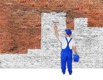 Anstreicher bedeckt Backsteinmauer mit weißer Farbe Stockfotografie
