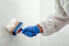 Anstreicher bei der Arbeit, die eine Wand mit einer Bürste malt stockfoto