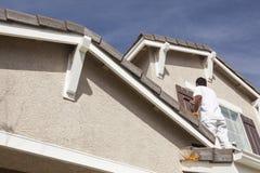 Anstreicher Painting die Ordnung und die Fensterläden des Hauses Stockfotografie