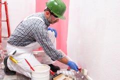 Anstreicherarbeitskraft bei der Arbeit in der Baustelle Geb?ude lizenzfreie stockfotografie