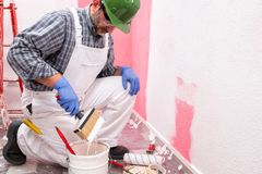 Anstreicherarbeitskraft bei der Arbeit in der Baustelle Geb?ude lizenzfreie stockbilder