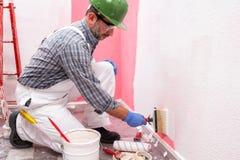 Anstreicherarbeitskraft bei der Arbeit in der Baustelle Geb?ude lizenzfreie stockfotos