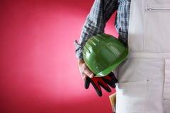 Anstreicherarbeitskraft mit Sturzhelm und Handschuhen in der Hand Gebäude lizenzfreies stockfoto