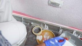 Anstreicherarbeitskraftmalerei die rosa Wand mit weißer Farbe Gebäude stock footage
