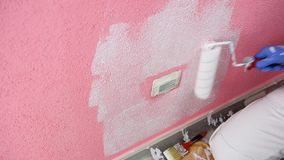 Anstreicherarbeitskraftmalerei die rosa Wand mit weißer Farbe Gebäude stock video