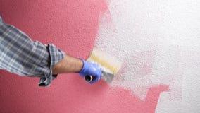 Anstreicherarbeitskraftmalerei die rosa Wand mit wei?er Farbe Geb?ude stock video