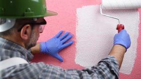 Anstreicherarbeitskraftmalerei die rosa Wand mit wei?er Farbe Geb?ude stock footage