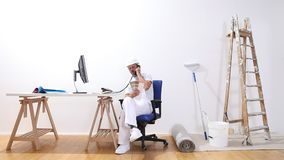 Anstreichermann mit einem Computergespräch am Telefon, Blicke auf Farbe probiert und macht einen TelefonKaufauftrag, E-Commerce stock video footage
