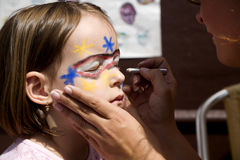 Anstrich der Schablone auf dem Gesicht des kleinen Mädchens Lizenzfreie Stockbilder