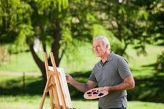 Anstrich des älteren Mannes im Garten stockbild