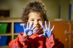 Anstrich des kleinen Mädchens mit den Händen im Kindergarten Stockfoto