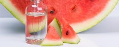 Anstrykning av den mogna vattenmelon i en genomskinlig flaska, på en vit bakgrund royaltyfri foto