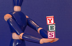 The Answer. Wooden blocks held by a wooden figure spell out the word yes Royalty Free Stock Image