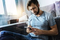 Low-spirited male person looking at his telephone. Answer message. Handsome man leaning on coach while sitting on the floor and reading news in internet Royalty Free Stock Photography