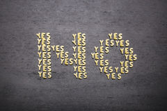 The answer no made up of a set of words yes, with small pasta letters on a dark background of a wooden board, showing the hidd Royalty Free Stock Images