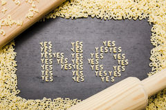 The answer no made up of a set of words yes, with small pasta letters on a dark background wooden board surrounded by other le Royalty Free Stock Photography
