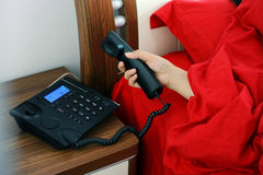 Answer phone. A girl offers her hand from quilt to answer a call royalty free stock image