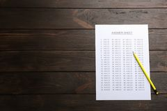 Answer sheet and pencil on wooden background, top view. With space for text royalty free stock image