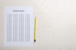 Answer sheet and pencil on wooden background, top view. With space for text royalty free stock photo