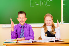 Answer. Students sit at their desk during a lesson and raise their hands to answer. Education stock photography