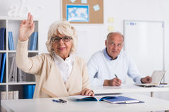Answering on the classes. Old women want to answer on the classes stock photo