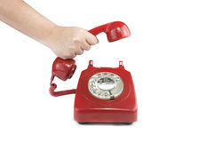Answering an old fashioned red telephone. Old fashioned 1970's or 50's style red telephone stock photos