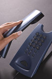 Answering phone. Hand picking up phone receiver Royalty Free Stock Images