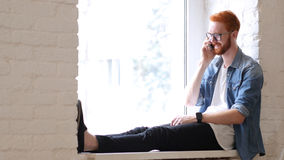 Answering Phone Call, Talk by Designer, Sitting in Window, Red Hairs and Beard Stock Photography