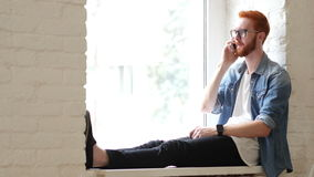 Answering Phone Call, Talk by Designer, Sitting in Window, Red Hairs and Beard. Creative designer , businessman stock footage