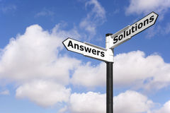 Answers and Solutions signpost. Signpost with the words Answers and Solutions against a bright cloudy sky stock photos