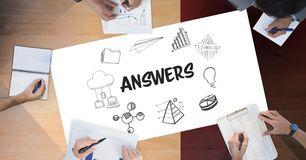 Answers text by icons and business people on table. Digital composite of Answers text by icons and business people on table Stock Photos